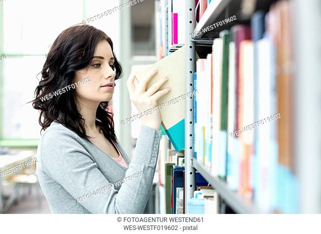 Student in a university library taking book from shelf