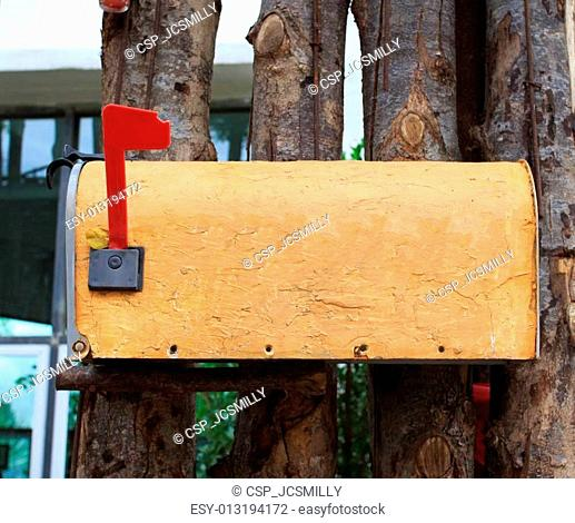 Old yellow mailbox on wood fence outdoor