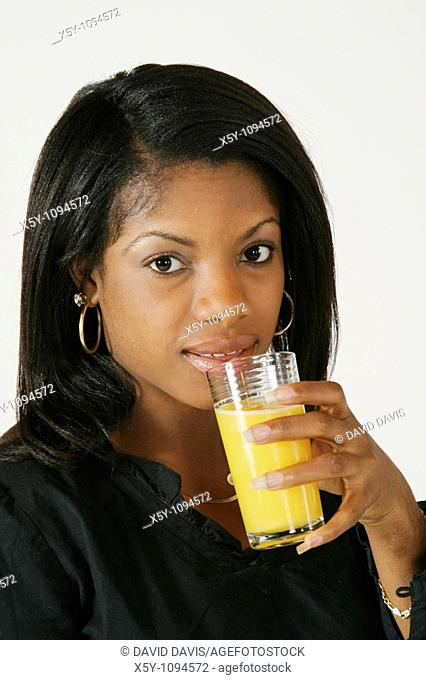 African American Woman in early 20's drinking orange juice