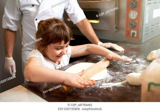 girl learns to roll out the dough