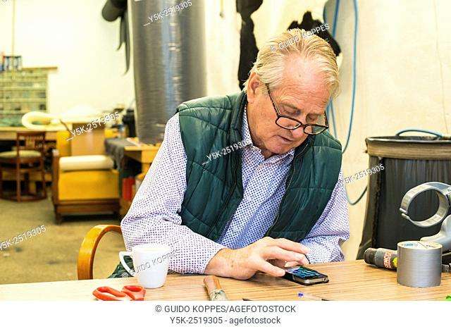 Tilburg, Netherlands. The 72 year old upholsterer Boy, reading the messages on his smartphone, while sitting at his workbench
