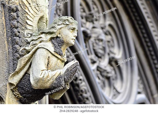 London, England, UK. St Matthew's Church, Bayswater. Limestone angel on facade showing 'black crust' or 'gypsum crust' caused by weathering