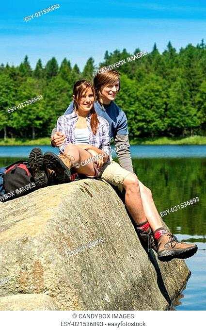 Young couple hikers lounging at lake nature