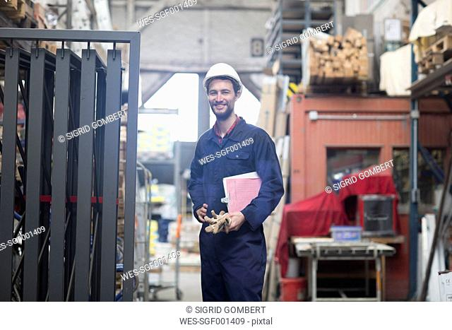 Smiling warehouseman with clipboard in storehouse