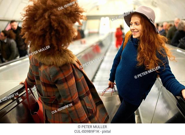 Two young women standing on moving escalator, elevated view