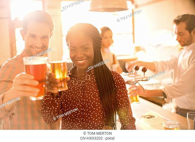 Portrait smiling couple toasting beer glasses at bar