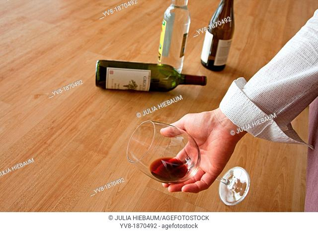 Drunken male holding a glass of red wine