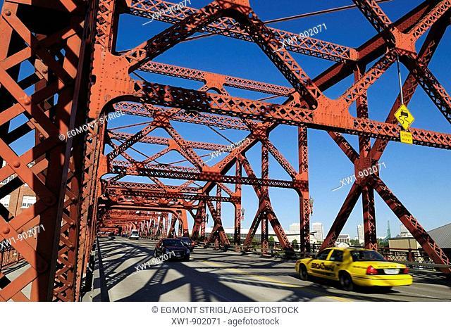yellow cab and cars crossing a historic steel bridge over Willamette River, Portland, Oregon, USA