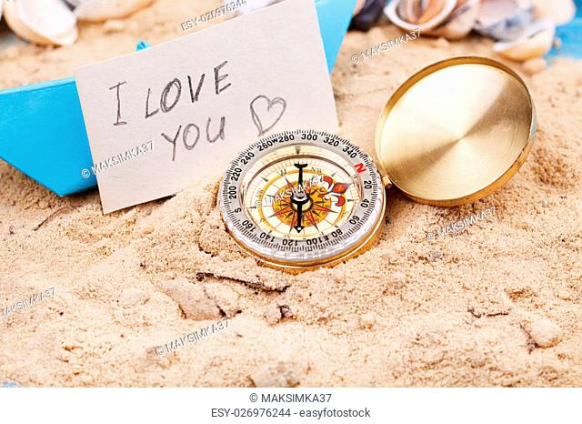 compass in the sand with sign - I love you