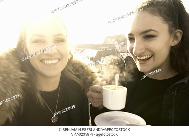 Two young sisters holding warm steaming coffee cup outdoors, Munich, Germany. Winter time, sunshine