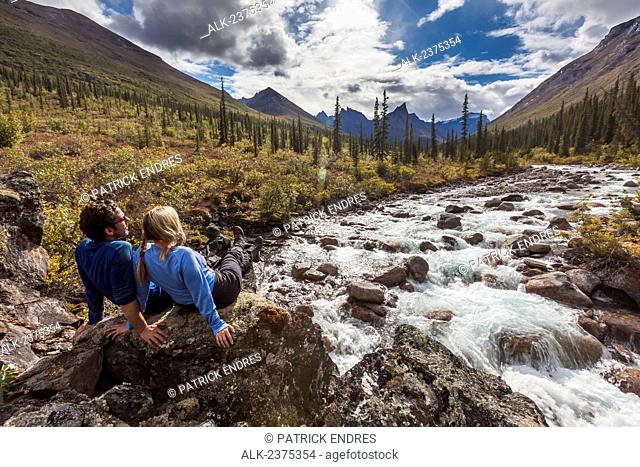 Couple relax next to Arrigetch creek with Xanadu, Elephant's Tooth and Parabala mountains in the distance, Arrigetch Peaks, Gates of the Arctic National park
