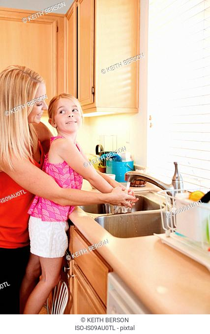 Mother washing daughter's hands in kitchen sink