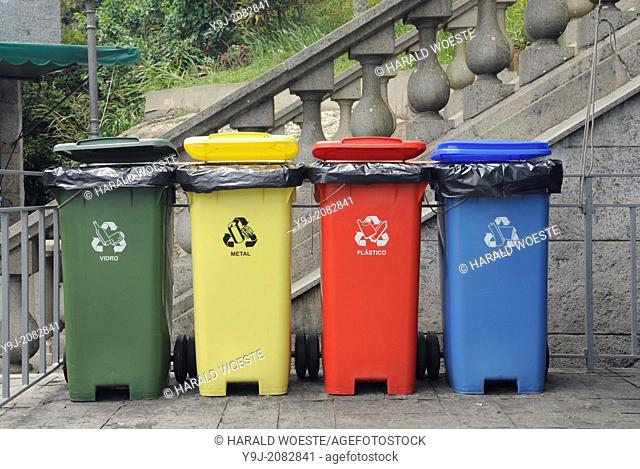Rio de Janeiro, Brazil. Four coloured waste bins lined up: green for glass (vidro), yellow for metal, red for plastics (plastico), blue for paper (papel)