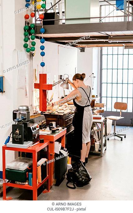 Female jeweller adjusting desk lamp at workbench