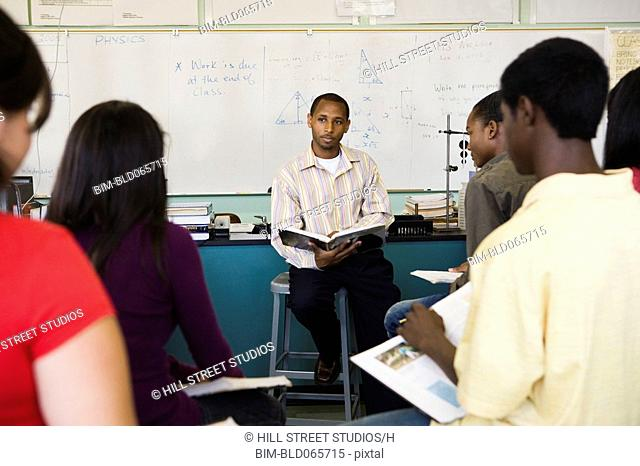 African teacher teaching students in chemistry lab