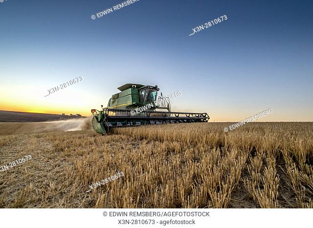 A combine harvester moving through a field of barley during a harvest in Reardan, Washington