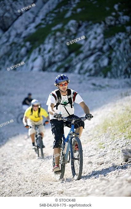 Three young men on mountainbikes in a rocky landscape, selective focus