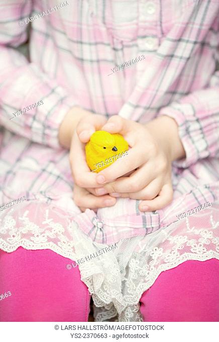 Hands of little girl holding plastic yellow bird