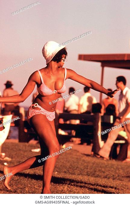 A smiling woman in a red gingham swimsuit and a white bucket hat enjoys Chicago's 12th Street Beach on Lake Michigan, Illinois, August, 1973