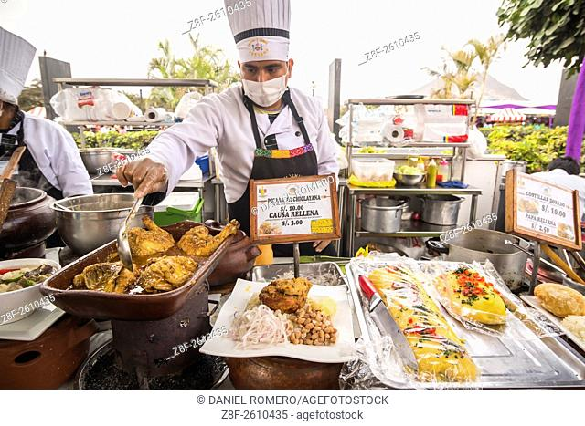 "Chef cooking chicken. Peruvian food dishes: """"Pollo a la Chiclayana"""", """"Causa Rellena"""". Peruvian seasoning and flavor, food fair"