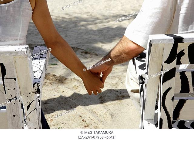 Rear view of a couple sitting on chairs and holding hands on the beach