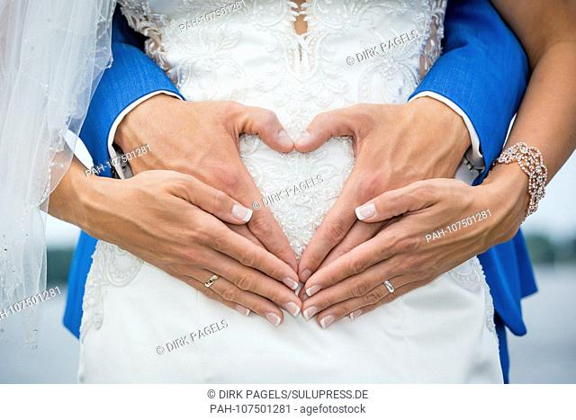 Detail of a bride and groom's hands at the wedding. The bride-and-groom embraces the bride from behind and forms her hands on her stomach into a heart