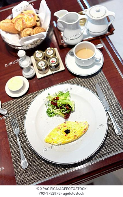 A complimentary Western styled breakfast consisting of a omelette, small side salad, croissants, and coffee