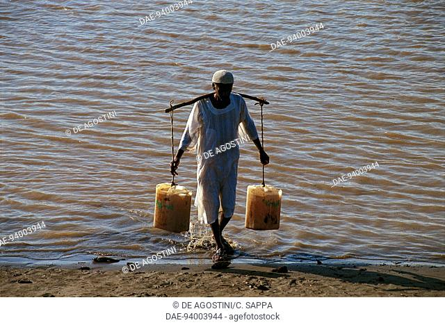 Man carrying two jerry cans of water out of the Nile river, near Karima, Nubia, Sudan