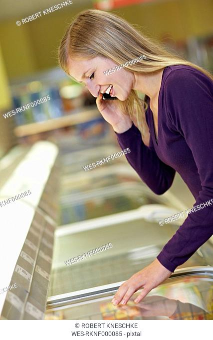 Germany, Cologne, Young woman standing at freezer in supermarket