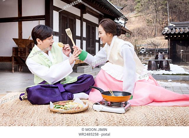 Side view of young couple in traditional Korean clothes cooking and tasting food