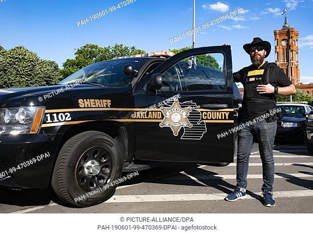 01 June 2019, Berlin: Gabor from Oranienburg stands next to his Chevrolet Tahoe (2011), a decommissioned former police vehicle in Oakland County (USA)