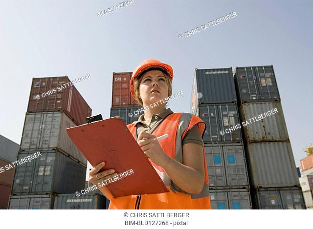 Woman wearing hard hat standing by shipping containers with clipboard