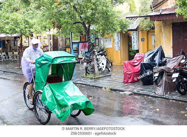Cyclo rider protected from the rains in Hoi An old town, Vietnam