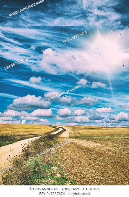 Beautiful windy countryside road against blue sky with clouds. Holiday and vacation concept