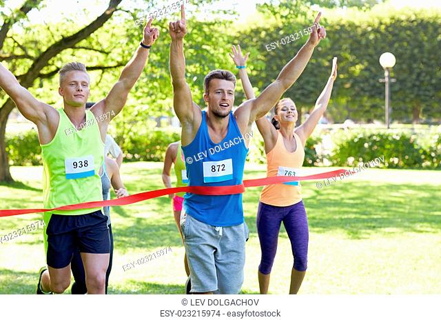 fitness, sport, victory, success and healthy lifestyle concept - happy man winning race and coming first to finish red ribbon over group of sportsmen running...