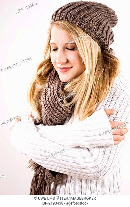 Smiling young woman wearing a hat and scarf, shivering
