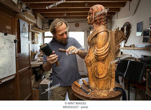 A wood carver standing in his workshop, using hand tools to shape and create decoration on a work in progress, a wooden female ship's figurehead