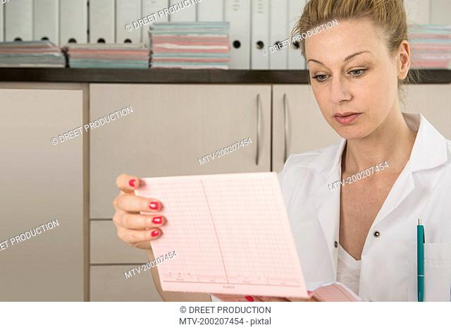 Female doctor reading the index card of a patient, Munich, Bavaria, Germany