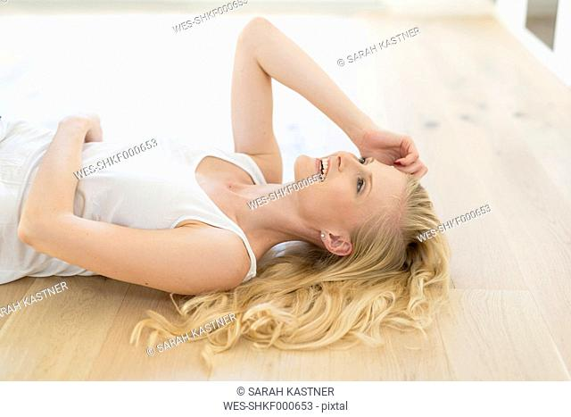 Smiling blond woman lying on wooden floor