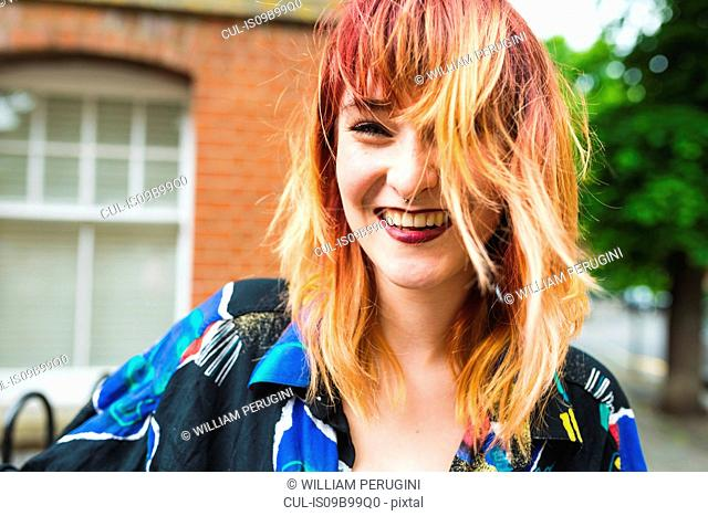 Portrait of young woman with dip dyed hair laughing