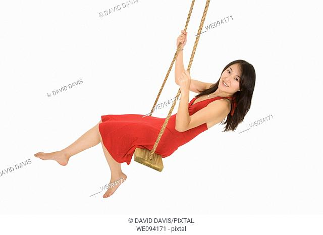 Caucasian Asian woman in wooden swing on white background