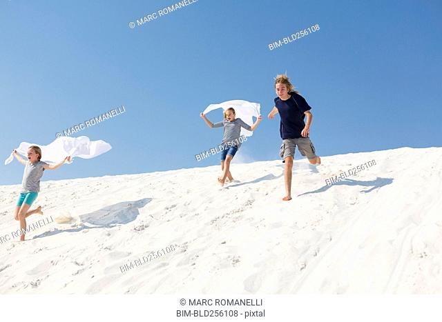Caucasian boy and girls running on sand dune