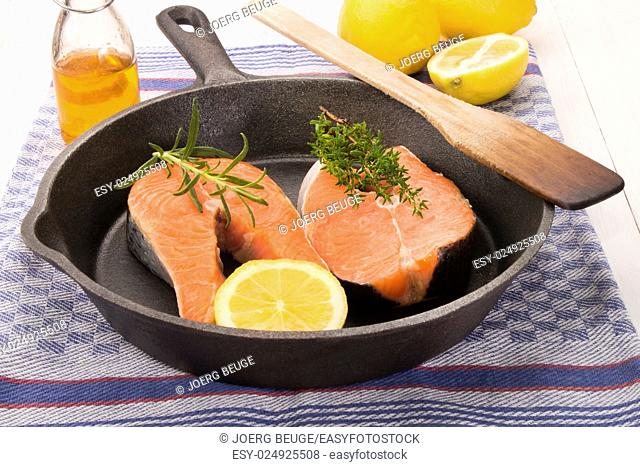 raw scottish salmon steak with lemon, thyme and rosemary in a cast iron pan