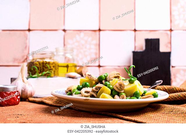 Octopus with vegetables in the plate on the table. Selective focus