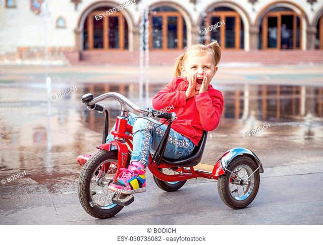 bf30c3fd6f8 Little girl in amusement park near fountain riding on tricycle and screaming