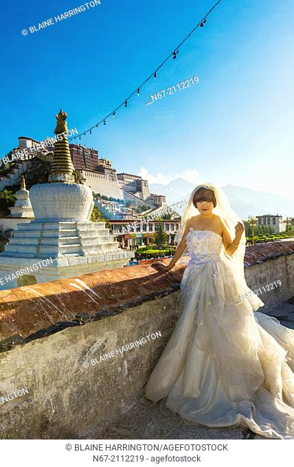 A Chinese bride posing in front of the Potala Palace, Lhasa, Tibet (Xizang), China