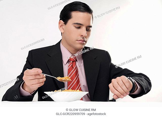 Businessman checking the time at breakfast table