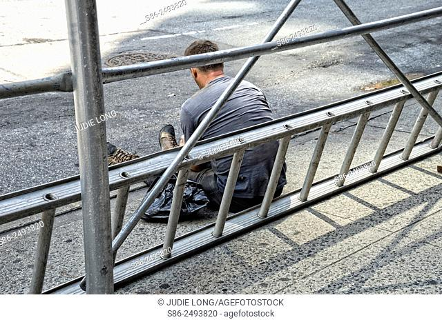 Workman Taking a Break and Leaning Against his Ladder and Scaffolding, on a New York City, Manhattan, Street