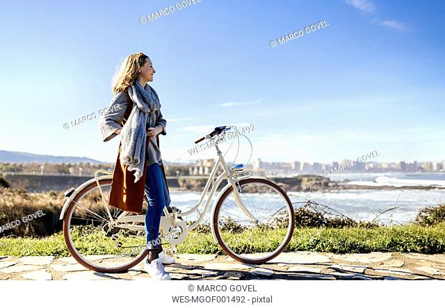 Spain, Gijon, smiling young woman on bicycle at the coast