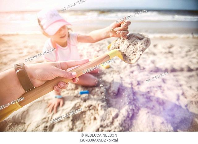 Personal perspective of mother on beach holding shovel of sand for daughter